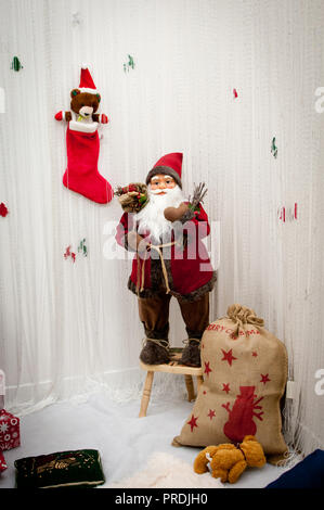 Christmas decoration, Santa Claus with bag of  gifts and teddy bear with hat in red sock on white background - Stock Photo