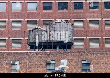 Water towers or rooftop Water Tank on an Apartment Building in New York. Deposits typical of a rooftop in the city of New York, USA. - Stock Photo