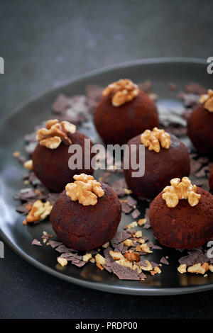 Rum balls are a truffle-like confection of sweet, dense cake flavored with chocolate and rum. Close-up on a dark plate of rum balls with wallnutsion d - Stock Photo