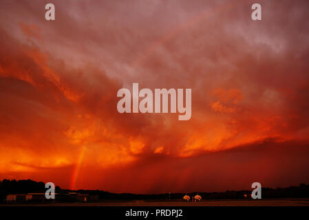 Rainbow over the Airport against the Backdrop of a Fiery Sunset in Front of a Storm. The State of Michigan, Grand Haven - Stock Photo