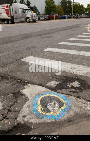 Detroit, Michigan - A pothole patched with an artistic mosaic of Aretha Franklin on a street in the Eastern Market district. Chicago artist Jim Bachor - Stock Photo