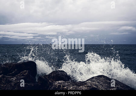 In the background, there are small yachts and a sea horizon. A large splash of water and a lot of drops took off and froze in the air. Dark illuminati - Stock Photo