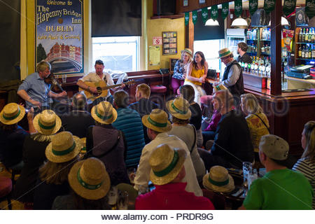 Two male musician guides performing traditional Irish music for a group of people inside the Ha'penny Bridge Inn, Temple Bar, Dublin, Leinster, Irelan - Stock Photo