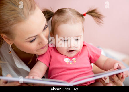 Beautiful mother is showing images in book to her little baby daughter at home. - Stock Photo