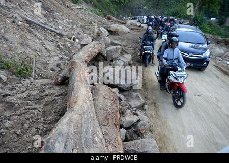 Palu, Indonesia. 1st Oct, 2018. People drive past debris of landslide after the earthquake in Palu, Central Sulawesi, Indonesia, Oct. 1, 2018. Over 1,203 people were killed in Palu, Donggala district, Parigi Mountong district and North Mamuju district, according to the Disaster Management Institute of Indonesia, Care for Humanity and the Humanity Data Center. Credit: Agung Kuncahya B./Xinhua/Alamy Live News - Stock Photo