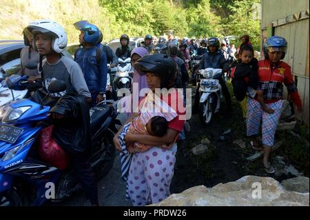Palu, Indonesia. 1st Oct, 2018. People wait to pass debris of landslide after the earthquake in Palu, Central Sulawesi, Indonesia, Oct. 1, 2018. Over 1,203 people were killed in Palu, Donggala district, Parigi Mountong district and North Mamuju district, according to the Disaster Management Institute of Indonesia, Care for Humanity and the Humanity Data Center. Credit: Agung Kuncahya B./Xinhua/Alamy Live News - Stock Photo