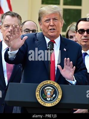 United States President Donald J. Trump answers reporter's questions following his remarks on the United States Mexico Canada Agreement (USMCA) in the Rose Garden of the White House in Washington, DC on Monday, October 1, 2018. The President also took questions on the Kavanaugh nomination. Visible behind the President are US Trade Representative Robert Lighthizer, left, and US Secretary of the Treasury Steven T. Mnunchin, right. Credit: Ron Sachs/CNP /MediaPunch - Stock Photo