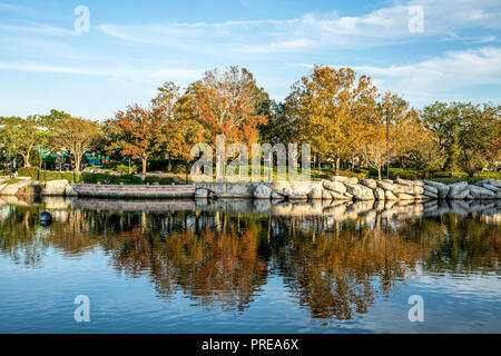 Upside down autumn trees with blue sky reflection in water. - Stock Photo