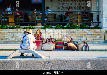 Mexican street vendor selling bags, waiting outside an expensive restaurant. Example of economic inequality.