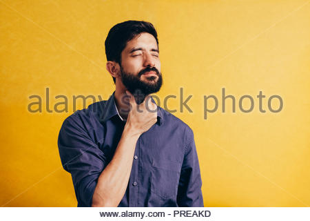 Young man having sore throat and touching his neck over yellow background. Hard to swallow - Stock Photo
