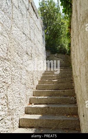 Old narrow staircase with stone wall on both sides, which leads up, illuminated by sunlight. - Stock Photo