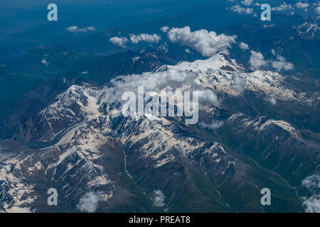 Aerial view of the Kazbek mountain and mountain range which partially covered by the snow on the top during the summer time - Stock Photo