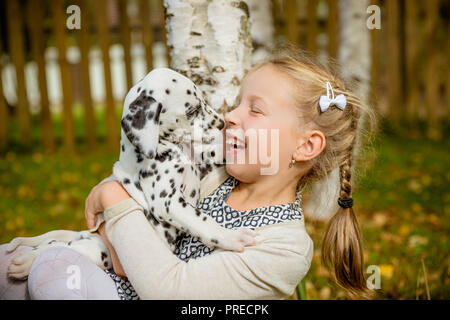 Little dog with happy owner spend a day at the park playing and having fun.Funny photo of laughing girl,she hugging and playing with beautiful Dalmatian puppy. Positive emotions of children fun games with home pet outdoor. - Stock Photo