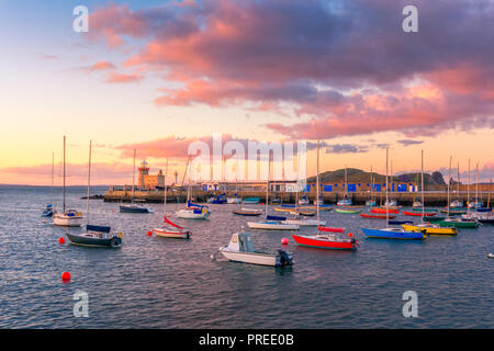 Amazing sunset in Howth, Dublin, Ireland. The view over Howth Lighthouse and colorful boats at the foreground. - Stock Photo