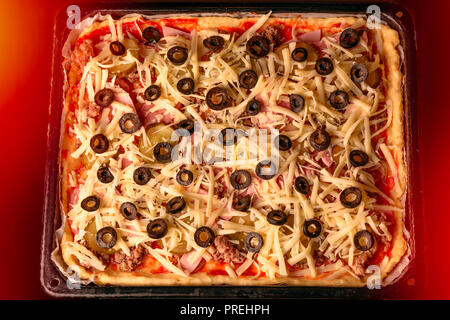 Homemade rectangular pizza with cheese, meat and olives on a baking sheet in a hot oven. Top view - Stock Photo