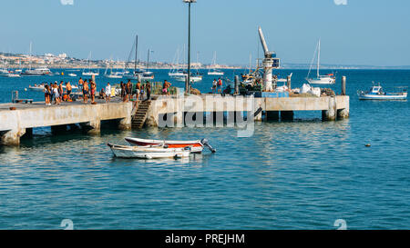 Cascais, Portugal - Sept 29, 2018: Young people jump off the pier onto Cascais Bay on a sunny summer day - Stock Photo