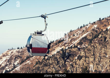 gray cable car over the mountains in Kazakhstan Almaty Medeo. - Stock Photo