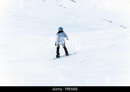 Snowboarder downhill on snowy off-piste slope in the evening light winter. - Stock Photo