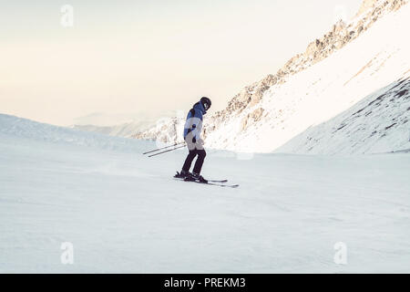 Skier skiing downhill in high mountains. The athlete is an Amateur, not a professional, cautious with the fear rolls down from the mountain. dilettant - Stock Photo