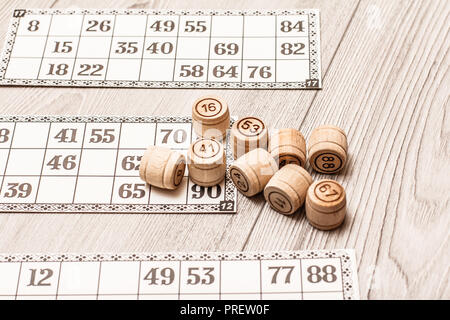 Board game lotto on white desk. Wooden lotto barrels and game cards for a game in lotto - Stock Photo