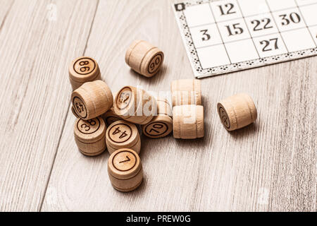 Board game lotto on white desk. Wooden lotto barrels and game card for a game in lotto - Stock Photo