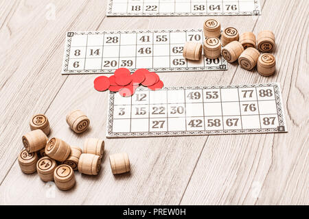 Board game lotto on white desk. Wooden lotto barrels, game cards and red chips for a game in lotto - Stock Photo