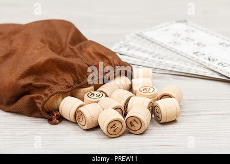 Board game lotto on white desk. Wooden lotto barrels with bag and game cards for a game in lotto - Stock Photo