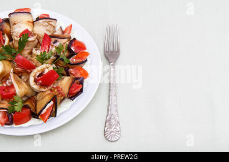 Dish of fried eggplant slices with tomatoes and cheese sauce decorated with parsley leaves on white plate - Stock Photo