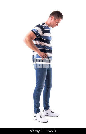 Side view of young disappointed sad man looking down with hands on hips. Full body isolated on white background. - Stock Photo