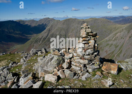 Cairn on Lingmell summit looking towards Kirk Fell and Pillar - Stock Photo