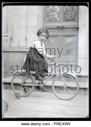 girl sitting on a bicycle with extra wheel support France circa 1920s - Stock Photo
