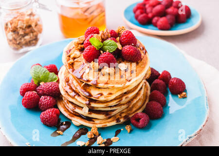Stacked american pancakes with raspberry and chocolate syrup, sprinkled with granola and decorated with mint leaves. Served on blue plate, on light st - Stock Photo