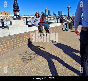 People sitting on the wall on the South Bank, London, England, UK. Lunchtime. City of London skyline behind - Stock Photo