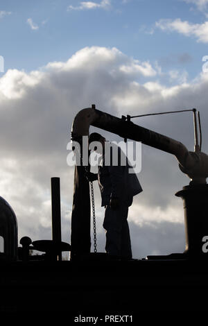 Close up of steam train driver, in silhouette against sky, stood on vintage locomotive operating water crane as engine takes on water in early evening. - Stock Photo