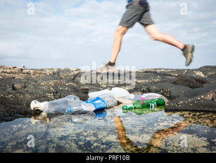 Low angle view of jogger running past plastic bottles in coastal beach rockpool, - Stock Photo