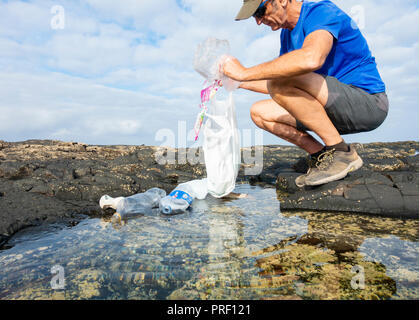 A Plogger/jogger collects plastic rubbish from beach rockpool during his morning run - Stock Photo