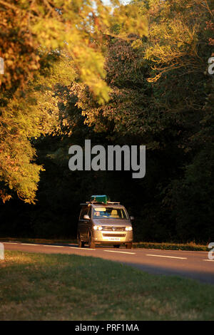 Cars driving along a country road in the Cotswolds. A very low setting sun makes pools of light against the darker shadows of the road behind. - Stock Photo