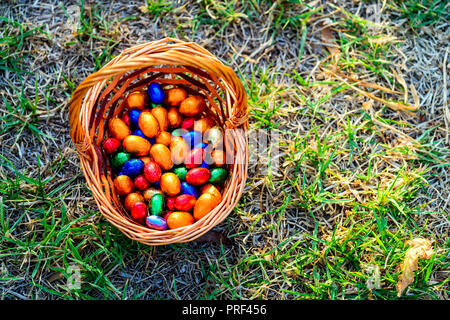 Colorful chocolate eggs in basket on grass - Stock Photo