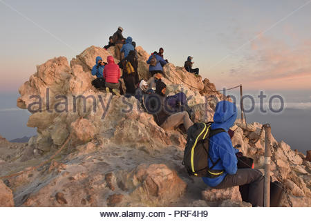 Hikers waiting for the sunrise on the top of Mount Teide volcano, 3718 m altitude, Teide National Park Tenerife Canary Islands Spain. - Stock Photo