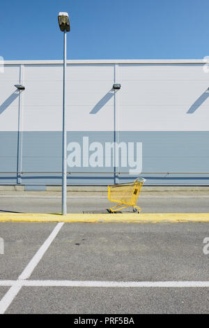 A lone single yellow shopping cart / trolley in an empty supermarket car park setting. - Stock Photo