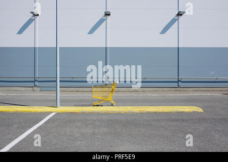A single yellow shopping cart / trolley in an empty supermarket car park setting. - Stock Photo