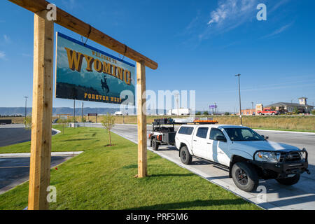 SEPTEMBER 14 2018 - LUSK, WYOMING: Welcome to Wyoming state border crossing welcome sign on a sunny day. White pickup truck in the photo - Stock Photo