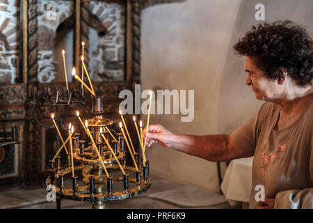 Senior woman lighting a candle in orthodox church. - Stock Photo