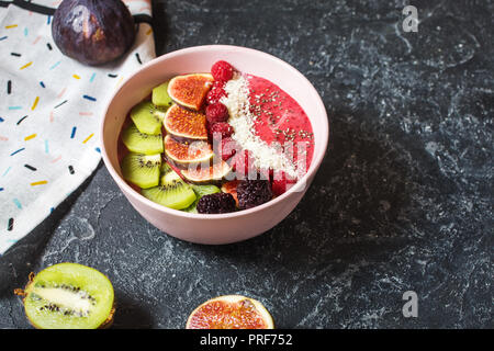 Raspberries smoothie bowl with figs, kiwi and coconut on concrete background. - Stock Photo