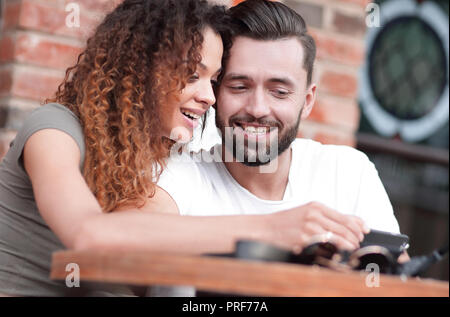 Happy loving  couple using a smartphone sitting in terrace - Stock Photo