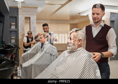 Three handsome barbers styling clients haircut in barbershop. Men wearing in striped coiffure capes. Professional hairstylists concentrated on cutting and grooming hair.  - Stock Photo