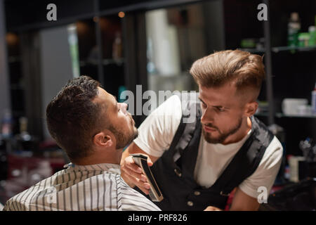 Concentrated and serious barber in white t shirt and vest holding trimmer. Handsome male hairdresser trimming client's beard. Bearded man sitting and holding head up.  - Stock Photo