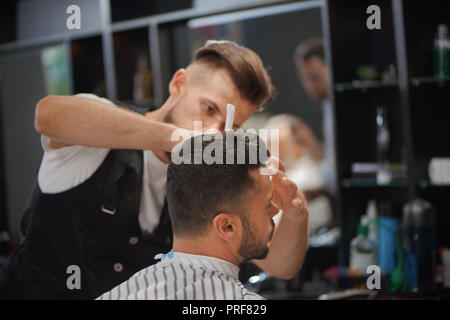 Confident male hairdresser styling man's beard and stylish haircut. Bearded client waiting while barber grooming his hair. Concept of barbershop, beauty and hair care. - Stock Photo