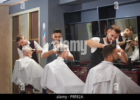 Process of three professional barbers working with clients' hair in barbershop. Clients wearing striped haircut gowns. Handsome hairdressers trimming, cutting and styling hair. - Stock Photo