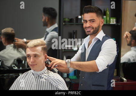 Handsome and confident barber trimming client's hair with trimmer. Bearded hairdresser in white shirt and vest looking at camera and smiling. Young man in haircut gown looking away. - Stock Photo